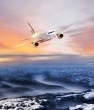 在天空的飞机在惊人的五颜六色的日落的冬天阿尔卑斯 免版税库存图片