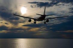 在天空的飞机飞行与在日落的美丽的云彩 免版税库存图片