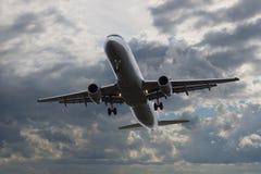 在天空的飞机飞行与在日落的美丽的云彩 免版税库存照片