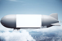 在天空的飞艇在城市上 图库摄影