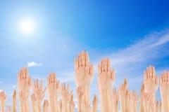 在天空背景的不同的被举的手 免版税库存图片