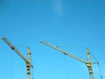 在天空背景的二个起重机塔 库存图片