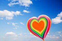 在天空背景的五颜六色的心形的棒棒糖 免版税库存照片