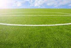 在天空背景的人为草皮橄榄球场绿色 免版税库存照片