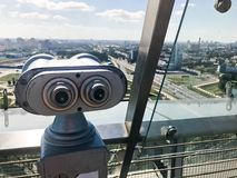 在天空背景的金钱固定式双筒望远镜  在观察平台的灰色金属双筒望远镜在高度屋顶 库存照片