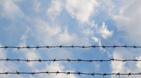 在天空背景的铁丝网 免版税库存照片