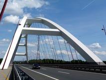 在天空蔚蓝下的白色篮子把柄曲拱吊桥 库存图片