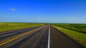 在天空蔚蓝下的空的西部得克萨斯高速公路 免版税库存图片