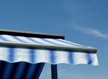 在天空蔚蓝下的蓝色和白色帆布遮篷 免版税库存图片