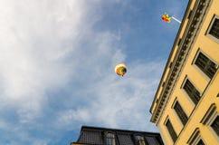 在天空蔚蓝在大厦,斯德哥尔摩的五颜六色的热空气气球, 免版税库存图片