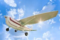 在天空蔚蓝白色云彩背景的上部翼飞机 免版税库存照片