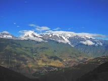 在天空蔚蓝的云彩在多雪的山 库存图片