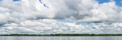 在天空蔚蓝的大白色云彩在河上 库存照片