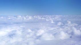 在天空蔚蓝的蓬松云彩从飞机窗口 从窗口飞行飞机的看法在天空蔚蓝的白色云彩中 天堂 股票录像