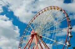在天空蔚蓝的观察轮子与白色云彩晴朗的夏日 库存图片