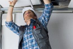 在天花板的电子工作者接线 库存照片