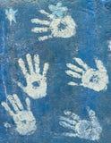 在天蓝色墙壁上的白色油漆handprints 库存照片