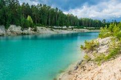 在天蓝色的池塘附近的沙滩 库存照片