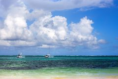 在天蓝色的海、加勒比海滩、天空蔚蓝和大白色云彩背景的两条小船 免版税库存照片