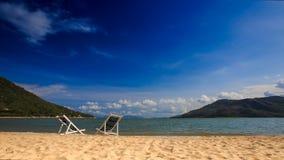 在天蓝色的海沙波海浪的两张海滩睡椅反对蓝天的 股票视频