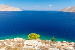在天蓝色的爱琴海的令人惊讶的看法从symi海岛,十二群岛,希腊 免版税库存照片