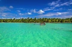 在天蓝色的水的白色小船在异乎寻常的棕榈树中 库存图片