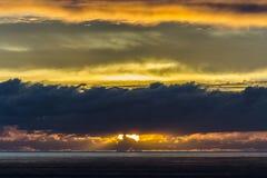 在天际的太阳设置与云彩 免版税库存图片