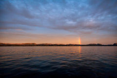 在天际的彩虹,反映在海 库存图片