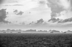 在天际的破烂物小船在下龙湾,越南,有在前景的在距离的雨和薄雾的 库存照片