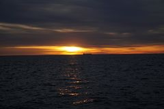 在天际的货船在日出 库存图片