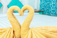 在天鹅心脏形状折叠的毛巾 免版税库存照片