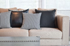 在天鹅绒灰棕色沙发的镶边和黑皮革枕头 免版税库存照片