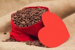 在天鹅绒红色囊旁边的红色纸心脏用咖啡豆 免版税库存图片