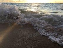在太平洋的日出光在海滩挥动在考艾岛海岛上的Kapaa在夏威夷 库存图片