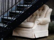 在太平门楼梯间下的被放弃的椅子 免版税库存图片