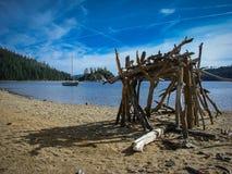 在太浩湖的鲜绿色海湾海滩的原始看的棍子小屋与一条风船的在湖的背景中 库存照片