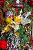 在太空人装饰品下的神仙的举行的圣诞节装饰品在折衷假日树 库存图片
