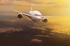 在太阳上升的天空的旅行的平面飞行 库存图片