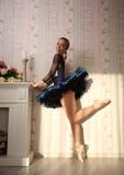 在太阳光的跳芭蕾舞者在家庭内部,站立在一条腿 库存照片