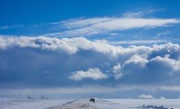 在太阳和云彩的冬天路 库存图片