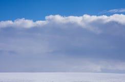在太阳和云彩的冬天路 免版税库存照片