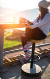 在太阳坐的妇女饮用的咖啡室外在轻的阳光下享用她的早晨咖啡 图库摄影