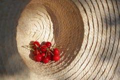 在太阳帽子的一些棵新鲜的樱桃 图库摄影
