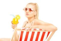 在太阳懒人和饮用的a的有吸引力的白肤金发的女性开会 库存照片