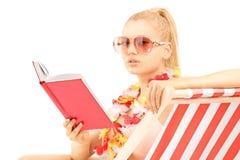 在太阳懒人和读书的有吸引力的白肤金发的女性开会b 免版税图库摄影