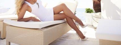 在太阳懒人的妇女腿 免版税图库摄影
