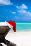 在太阳椅子的圣诞节帽子在热带海滩 免版税库存照片