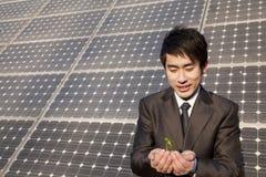 在太阳电池板前面的商人托起的植物 库存图片