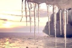 在太阳的美好的冰柱亮光反对日落 在贝加尔湖的冬时 库存图片