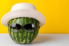 在太阳镜和一个夏天帽子的西瓜在明亮的黄色背景 免版税库存图片